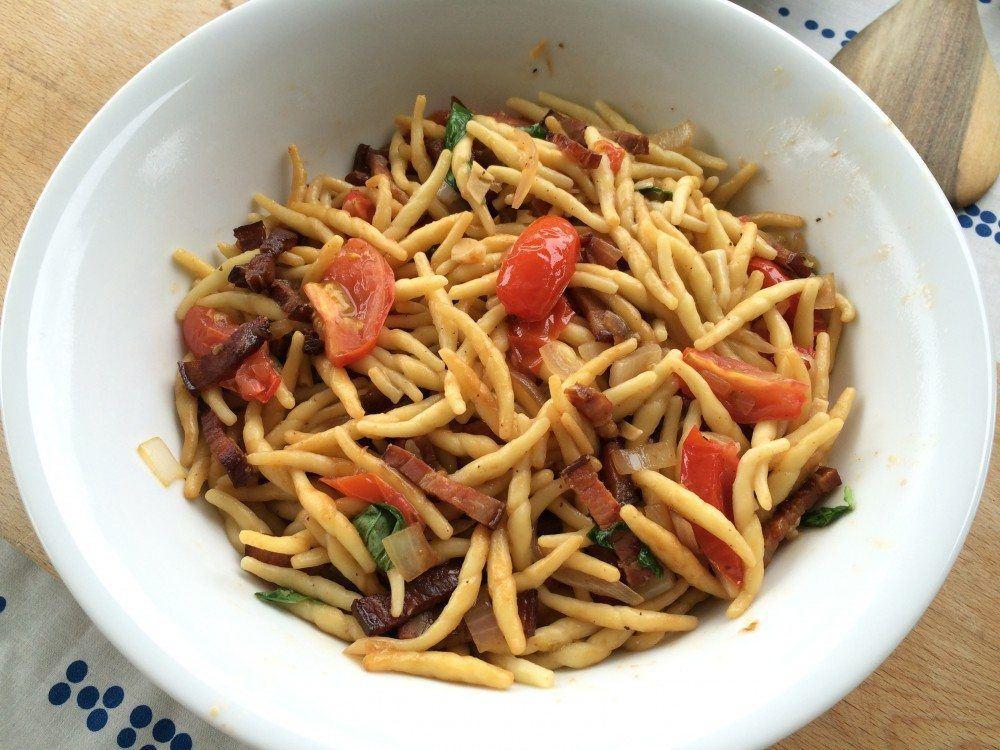 Den færdige pastaret med bacon serveres med et stykke brød til.