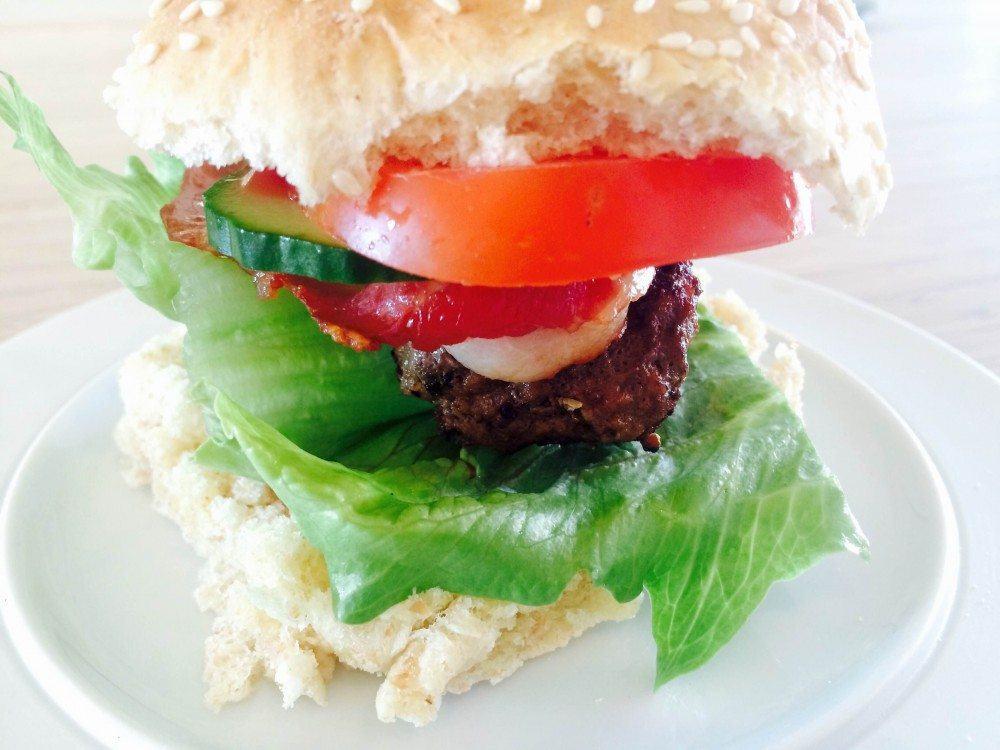 Put din burgerbøf af oksekød godt af vejen i en lækker hjemmebagt burgerbolle, salat, tomat, agurk, rødløg og lidt bacon. Foto: Guffeliguf.dk.