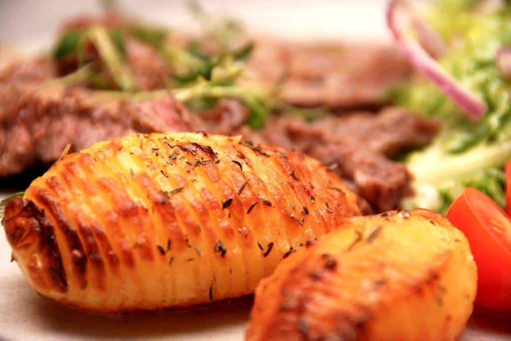 Hasselback kartofler (hasselbagte kartofler) er blandt andet gode til en bøf med salat og tomater. Foto: Madensverden.dk.