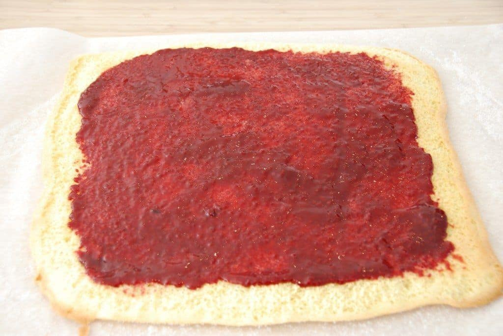 Smør marmelade ud på den bagte dej. Smør godt ud til kanterne, men pas også på det ikke bliver for tykt et lag marmelade. Foto: Guffeliguf.dk.