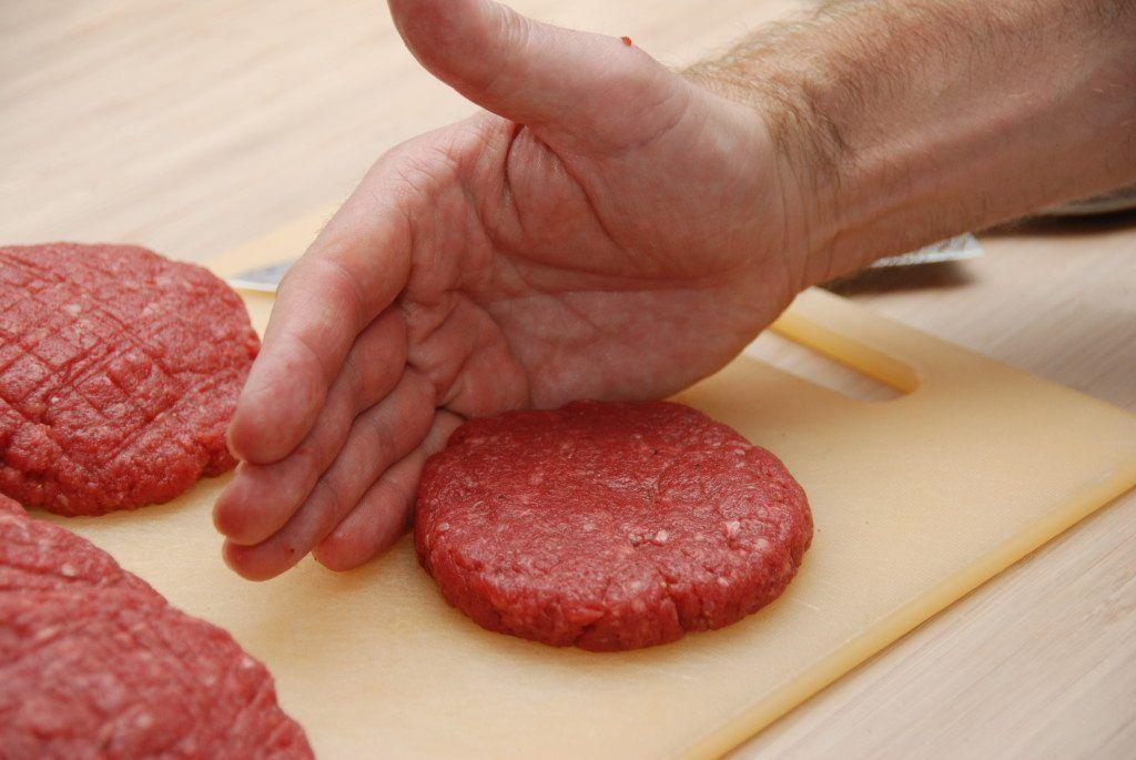 Sådan skal du forme en hakkebøf. Støt kanten af bøffen med den ene hånd, mens du med fingrene på den anden hånd trykker din hakkebøf rund ud til kanten. Foto: Guffeliguf.dk.