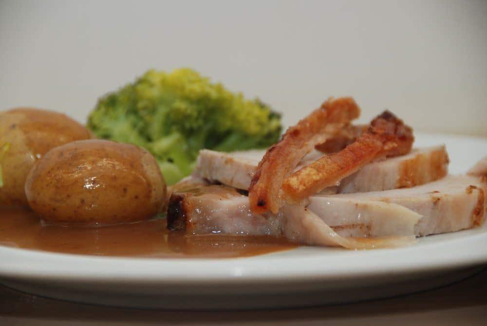 Flæskesteg i ovn med sprød svær og en super dejlig flæskestegssovs. Serveret med kogte kartofler og broccoli. Foto: Guffeliguf.dk.