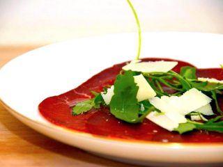 Bresaola er en smuk spise med sin meget mørkerøde farve. Bresaolaen anrettes med rucola og parmesan. Giv den også lidt trøffelolie. Foto: Madensverden.dk.