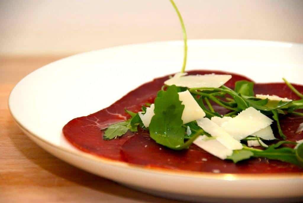 Bresaola er en smuk spise med sin meget mørkerøde farve. Bresaolaen anrettes med rucola og parmesan. Giv den også lidt trøffelolie. Foto: Guffeliguf.dk.