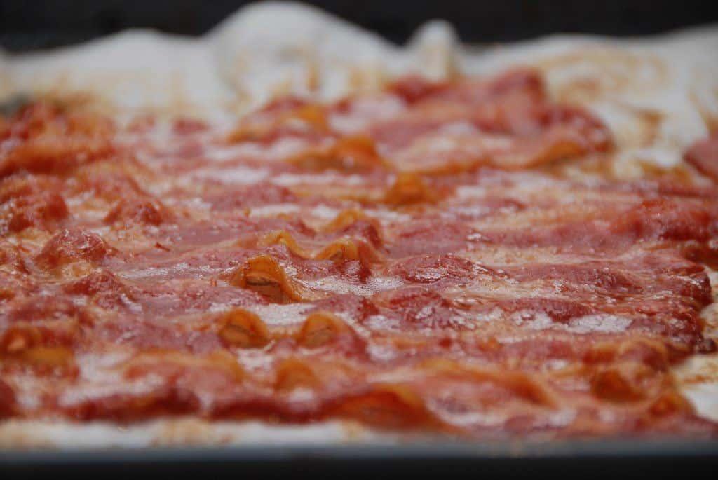 Bacon i ovn steger du ved at lægger baconskiverne tæt. De må gerne overlappe lidt, men ikke for meget. Foto: Madensverden.dk.