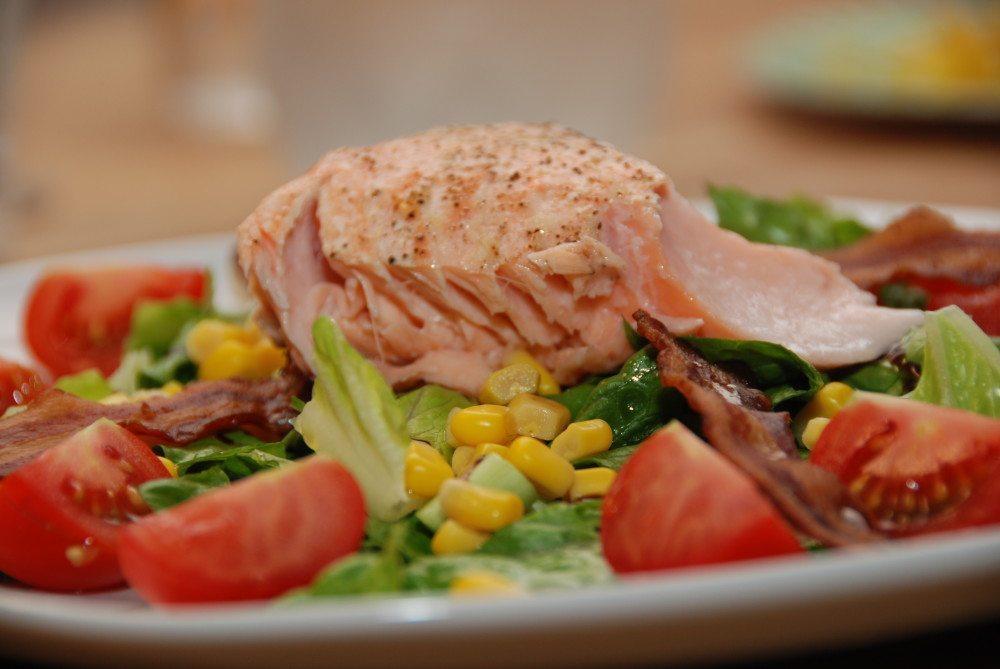 Laksesalat er både sund og nem aftensmad, som du laver med laks, der er bagt i ovnen. Anrettes på en frisk salat med tomater og sprød bacon. Foto: Guffeliguf.dk.