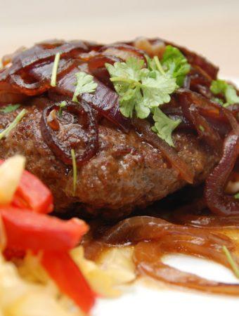 Hakkebøffer med karamelliserede rødløg er det mums! Disse hakkebøffer er lavet i ovnen, så du får saftigt kød og en helt fantastisk sovs - med rødløg. Foto: Madensverden.dk.
