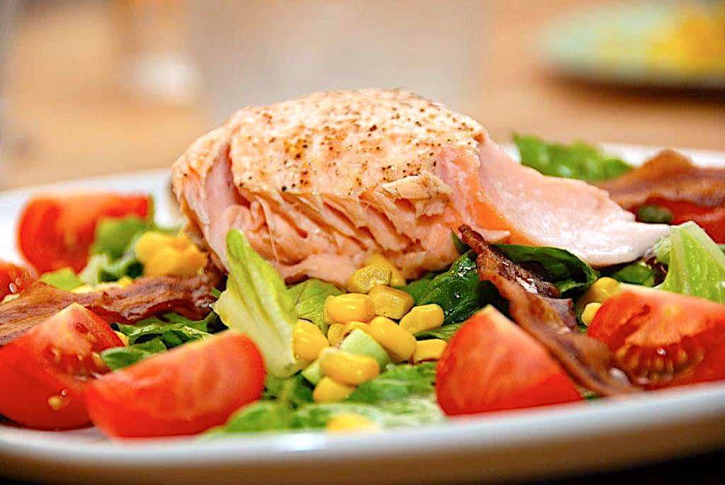 Laksesalat er både sund og nem aftensmad, som du laver med laks, der er bagt i ovnen. Anrettes på en frisk salat med tomater og sprød bacon. Foto: Holger Rørby Madsen, Madensverden.dk.