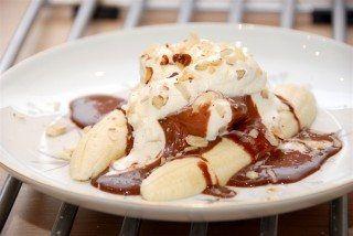Banana split med hjemmelavet chokoladesauce er en fantastisk dessert, der laves med banan, is, chokoladesauce og hasselnøddeflager. Foto: Guffeliguf.dk.