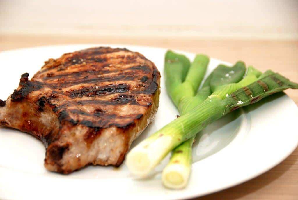 Store grillkoteletter med ben og grillede forårsløg