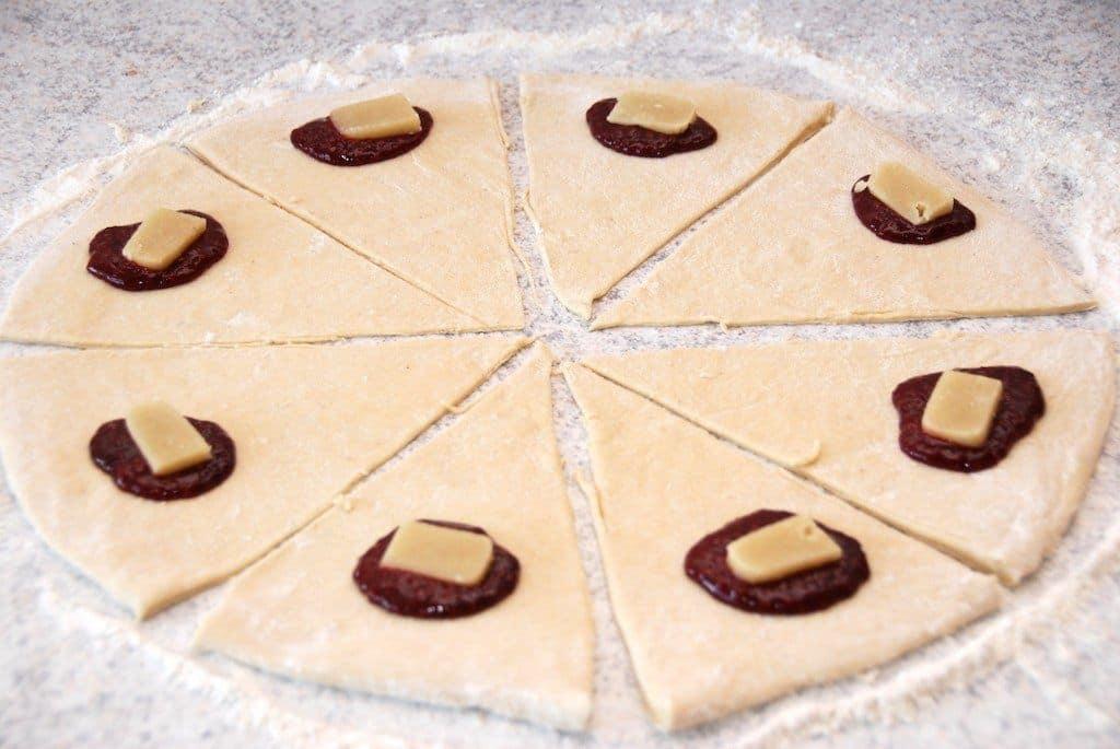 Kærnemælkshorn laves af en dejcirkel, der udskæres i otte stykker. Kom en klat hindbærmarmelade og marcipan på hvert stykke. Foto: Guffeliguf.dk.