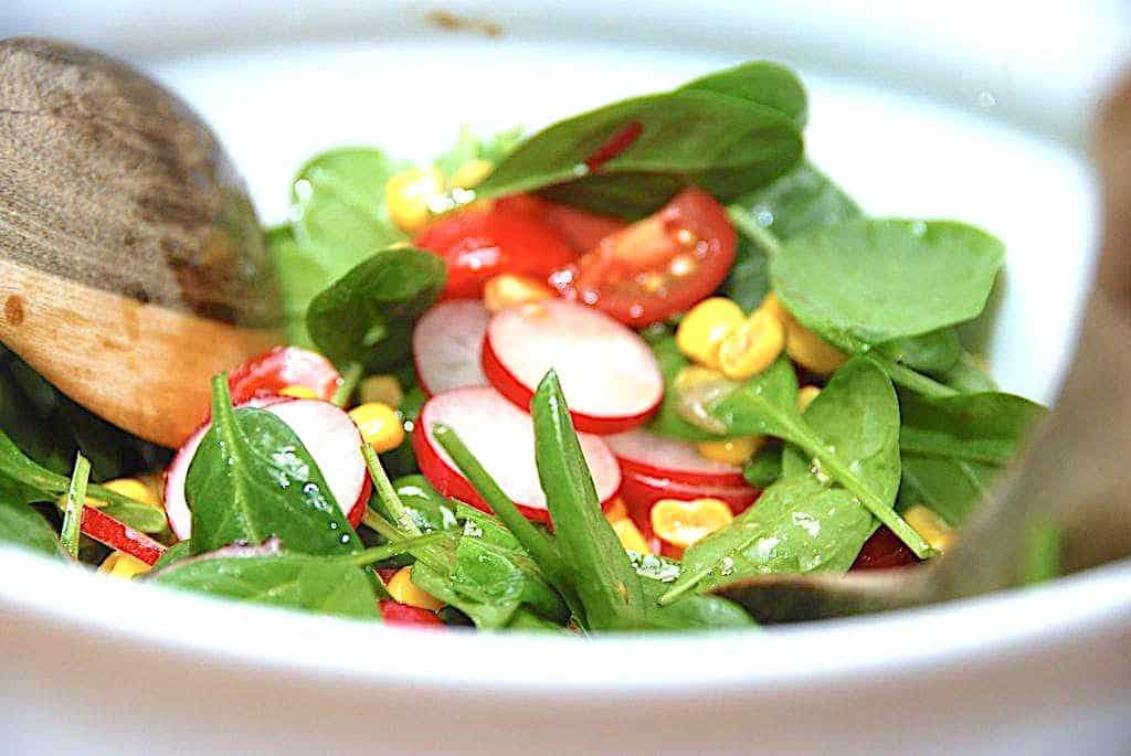 Salat med radiser, spinat, majs og tomater