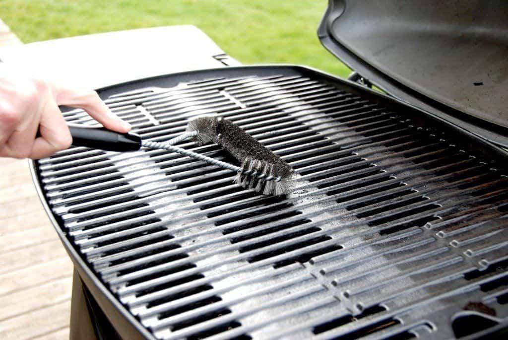 Du rengør risten i en Weber Q3200 gasgrill med en grillbørste, som du bruger mens grillen stadig er varm. Foto: Madensverden.dk.