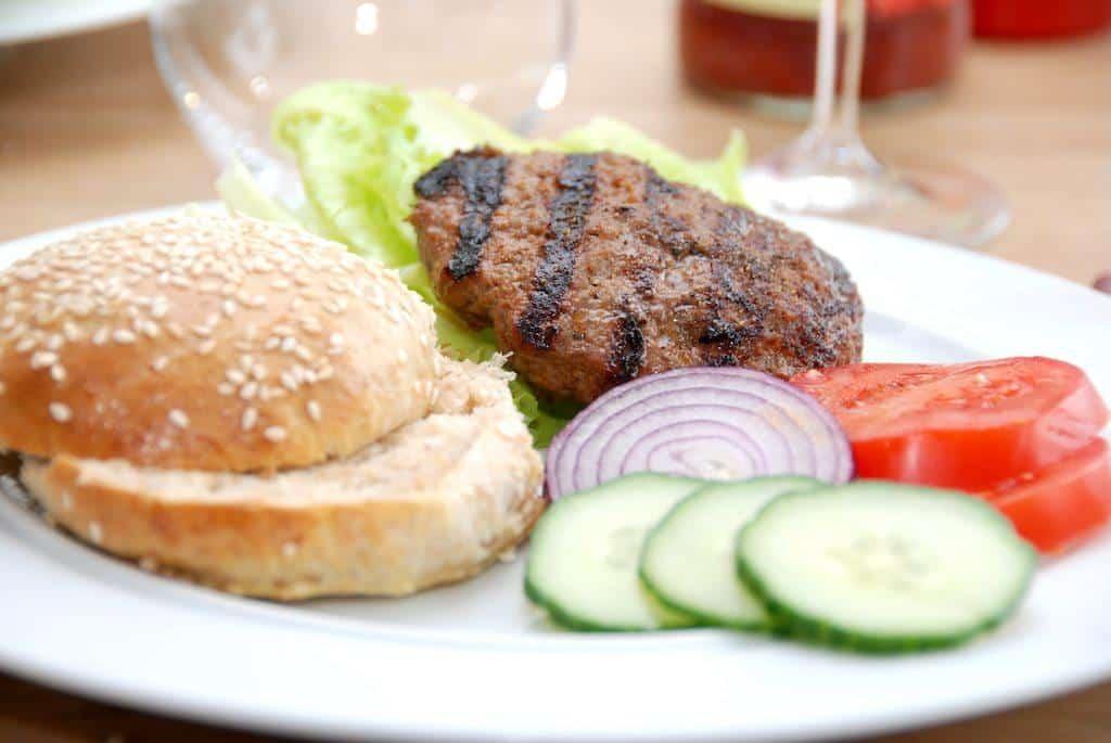 Hjemmelavede fuldkorns burgerboller og bøffer, der selvfølgelig serveres med icebergsalat, agurk, rødløg og tomater. Foto: Guffeliguf.dk.