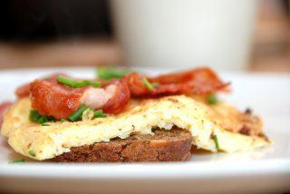 Luftig omelet med god bacon og purløg - serveret på et stykke rugbrød. Foto: Guffeliguf.dk.