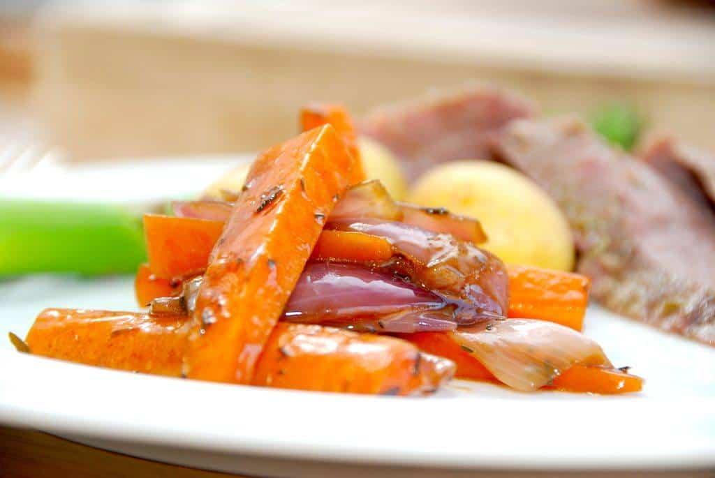Glaserede gulerødder og rødløg er flot tilbehør på en tallerken. Her serveret til en flanksteak i ovn. Foto: Guffeliguf.dk.
