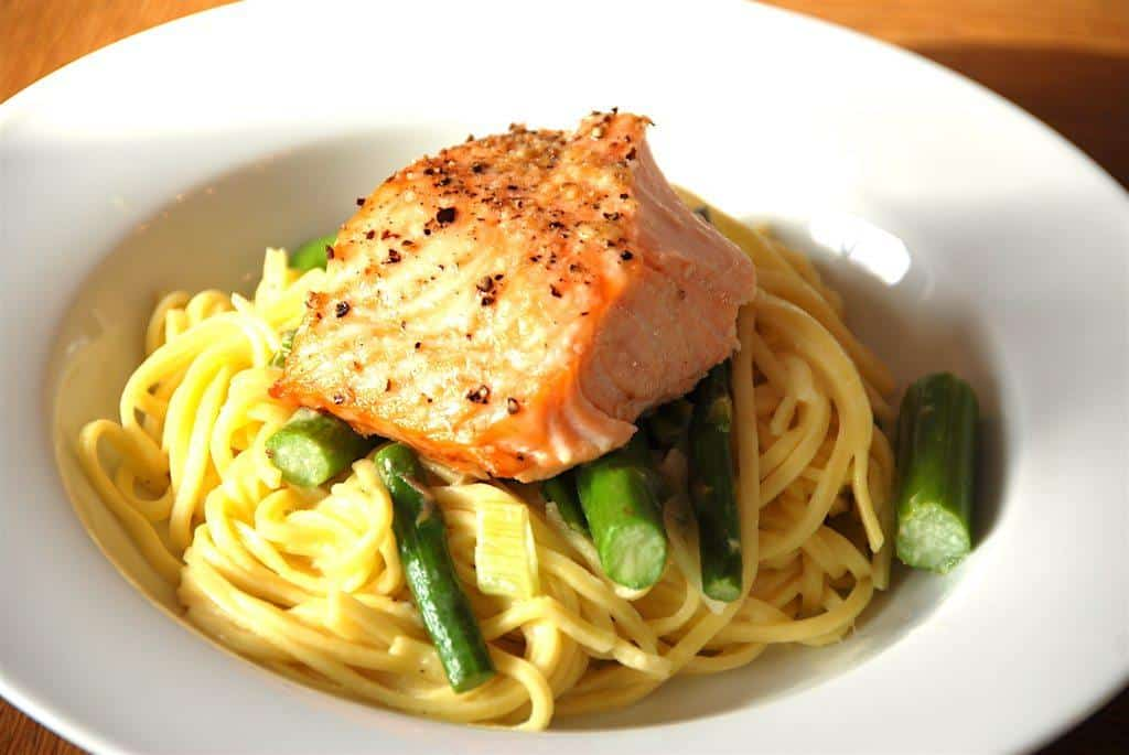 Dejlig pasta med laks, der tilberedes med forårsløg og grønne asparges. En hurtig og sund ret på travle dage. Foto: Madensverden.dk.