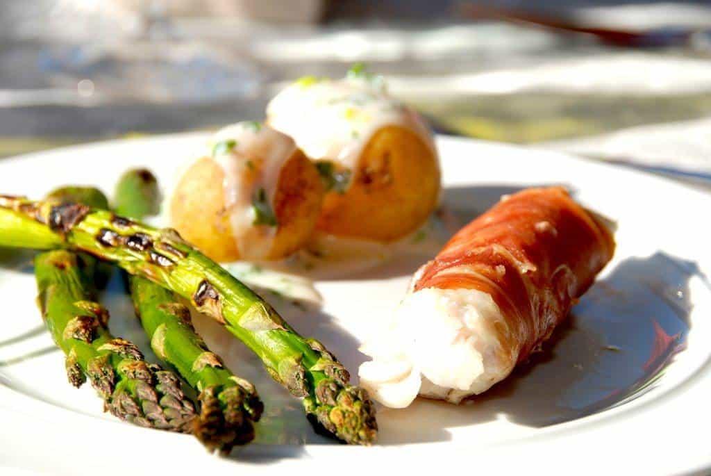 Grillede torskeruller er hurtig mad på grillen med benfri torskefilet, der omvikles med parmaskinke. Serveres med grillede grønne asparges, nye kartofler og en god persillesovs. Foto: Guffeliguf.dk.