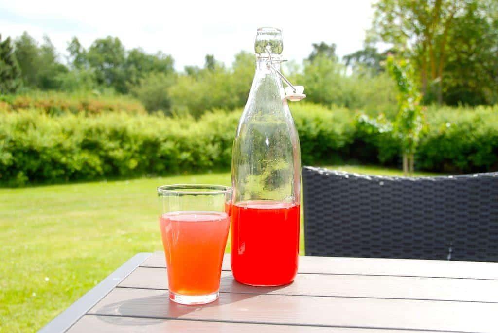 Jordbærsaft er en vaskeægte sommerdrik, som her er smagt til med friske hyldeblomster. Så bliver det ikke mere sommeragtigt. Foto: Guffeliguf.dk.