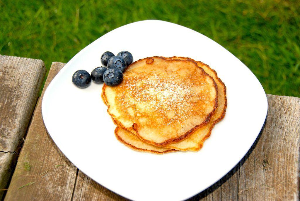 Lækre amerikanske pandekager, der drysses med lidt flormelis og serveres med friske blåbær. De små pandekager er gode til morgenbordet. Foto: Guffeliguf.dk.