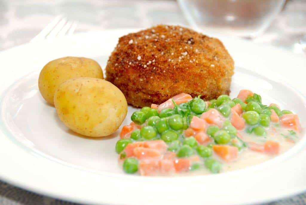 Karbonader i ovn bliver både sprøde og saftige. Karbonaderne paneres først, og steges først på panden inden turen i ovnen. Her serveret med stuvede ærter og gulerødder. Foto: Guffeliguf.dk.