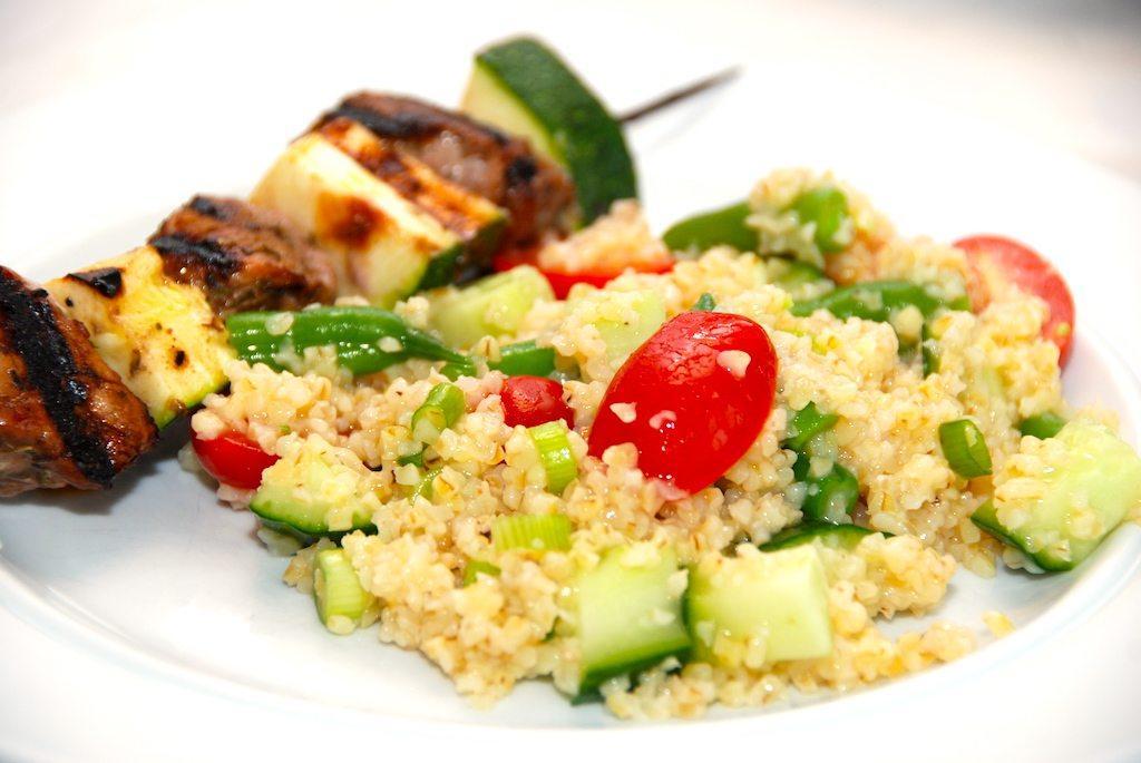 En sund og dejlig bønnesalat med bulgur. Der skal også tern af agurk, halve Angelle tomater og lidt skiver af forårsløg i salatskålen. Foto: Guffeliguf.dk.