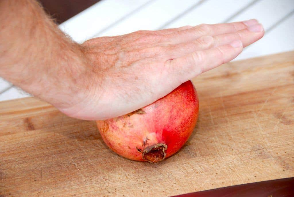Start med at trille granatæblet hårdt mod et skærebræt eller bordet. På den måde får du løsnet kernerne fra hinderne, og dermed er de meget nemmere at få ud. Du kan høre kernerne nærmest knase sig løse, så fortsæt indtil du fornemmer at alle kernerne er blevet løsnet. Foto: Guffeliguf.dk.