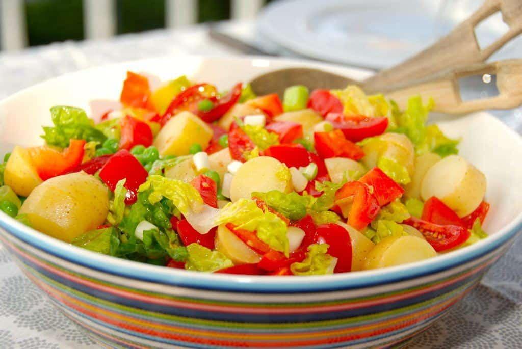 En lækker kartoffelsalat opskrift der, udover kartofler, indeholder hjertesalat, tomater, ærter og forårsløg. Slut af med at vende en skøn dressing sammen med kartoffelsalaten. Foto: Guffeliguf.dk.