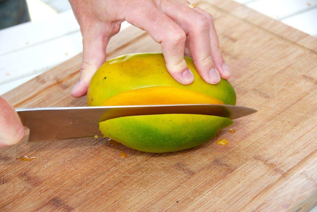 Den korrekte mango udskæring. Start med at skære en skive af mangoen tæt op ad stenen. Foto: Guffeliguf.dk.