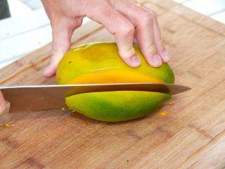 Den korrekte mango udskæring. Start med at skære en skive af mangoen tæt op ad stenen. Foto: Madensverden.dk.