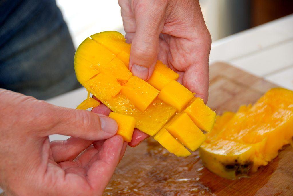 Derefter er det meget nemt at pille ternene af skrællen, og så er der ellers friskskåret mango. Nemmere bliver det ikke med en mango udskæring. Foto: Guffeliguf.dk.