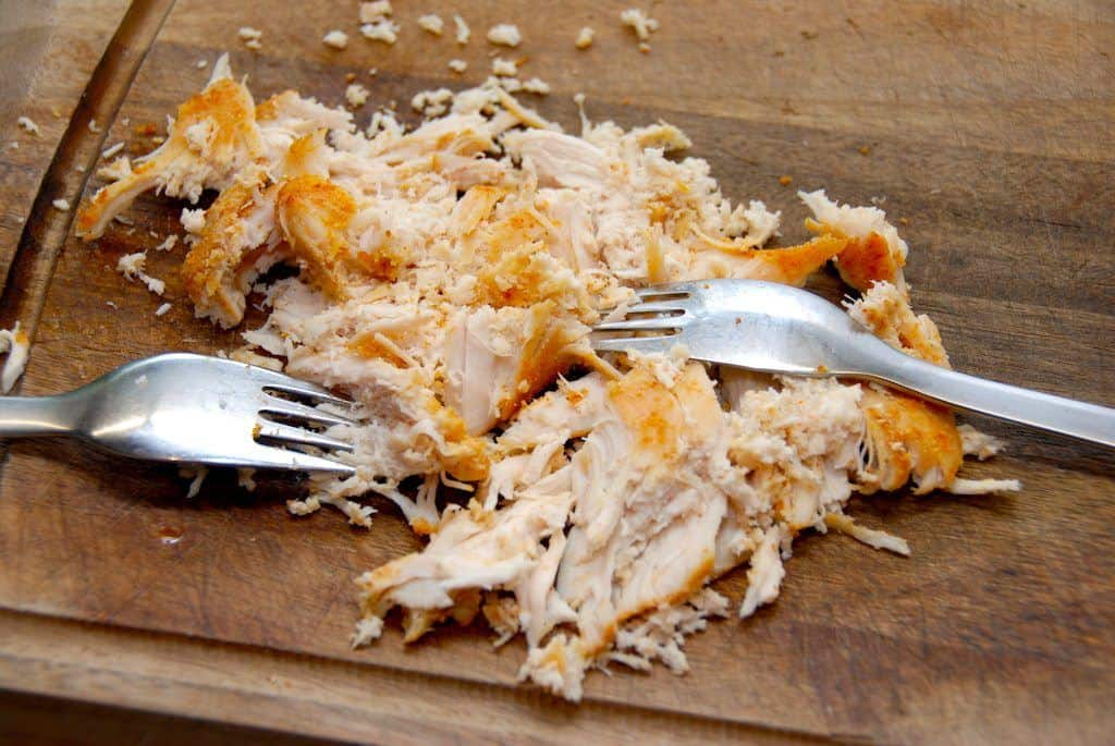 Pulled chicken er langtidsstegt kylling, som du efter tre timer i ovnen trækker fra hinanden med et par gafler. Den trevlede kylling kan spises som den er, eller bruges i en salat eller burger. Foto: Guffeliguf.dk.