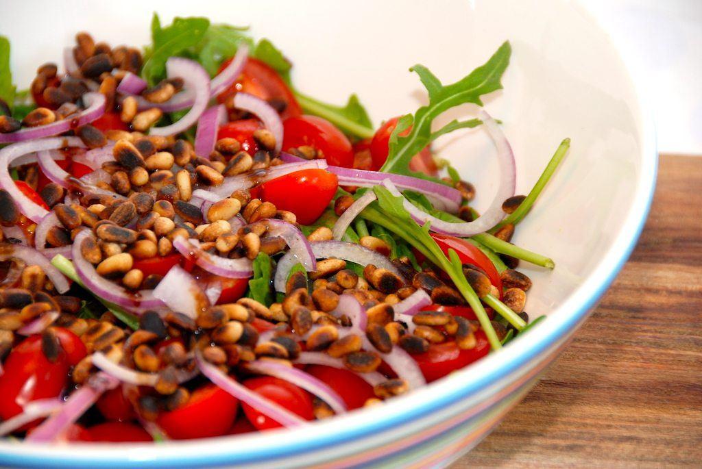 En lækker og sprød rucolasalat med pinjekerner, der selvfølgelig er ristet på panden. Kom også finthakket rødløg og små tomater i salatskålen, og dryp lidt olivenolie på til sidst. Foto: Guffeliguf.dk.