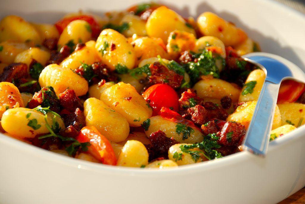 Gnocchi med chorizo er lækkert tilbehør til blandt andet kylling. Gnocchi er lavet af kartofler, og i denne ret koges gnocchien først i vand, inden den sauteres på panden med chorizo, rødløg, tomater og friskhakket persille.Retten kan også stå alene. Foto: Guffeliguf.dk.