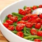 Ovntomater er et perfekt match med letkogte grønne bønner i denne salat. Tomat- og bønnesalaten er en god ledsager til en grillet bøf. Foto: Madensverden.dk.