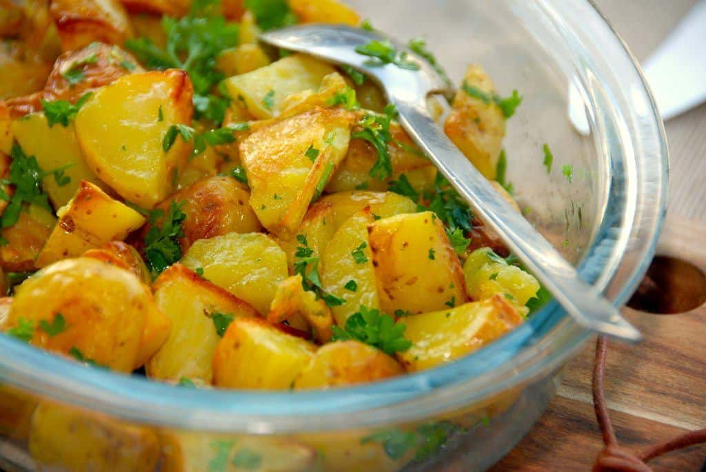 gode og nemme ovnstegte persillekartofler, der smager super godt til blandt andet frikadeller. Kartoflerne steges i ovnen, og vendes efterfølgende med persille. Foto: Guffeliguf.dk.