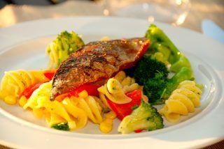 Lækker og skindstegt makrelfilet, der steges på panden med knuste hvidløg. Makrelfileterne steges på skindsiden i tre minutter, inden de får 10 sekunder på kødsiden. Her serveret med en lun pastasalat med friske majs og broccoli. Foto: Guffeliguf.dk.
