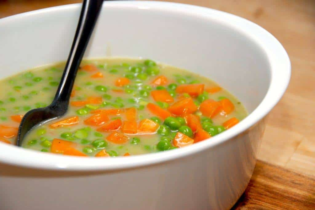 Stuvede ærter og gulerødder jævnet med smørbolle