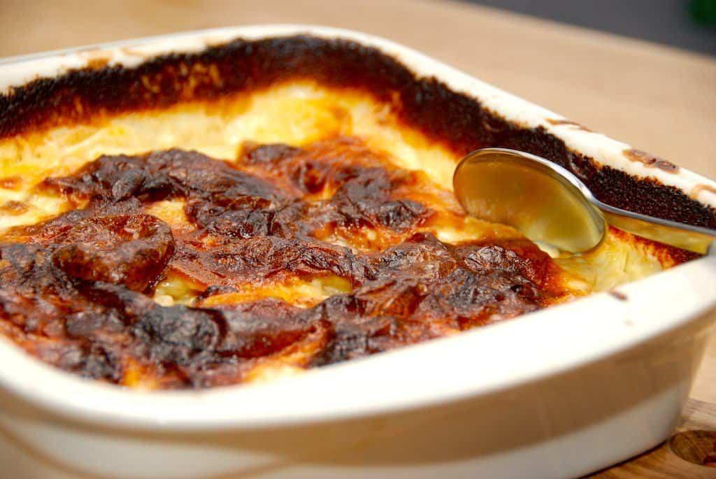 Dejlige og meget cremede flødekartofler i ovn, der laves med lidt selleri. Du kan dog udelade sellerien, og i stedet komme lidt flere kartofler i. Læg mærke til den mørke overflade på flødekartoflerne. Den giver masser af smag, og sådan skal den være. Foto: Madensverden.dk.