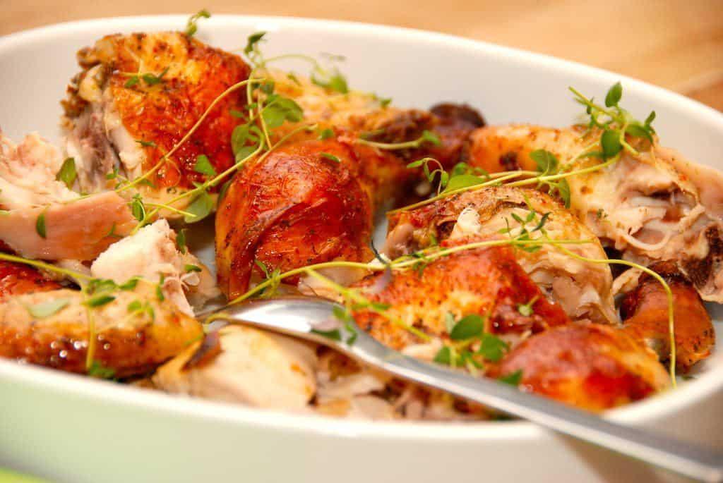 En god opskrift på hel kylling med karrysovs, der kan serveres med kogte ris. Steg kyllingen i en stegepose i ovnen, og server med frisk timian. Foto: Guffeliguf.dk.