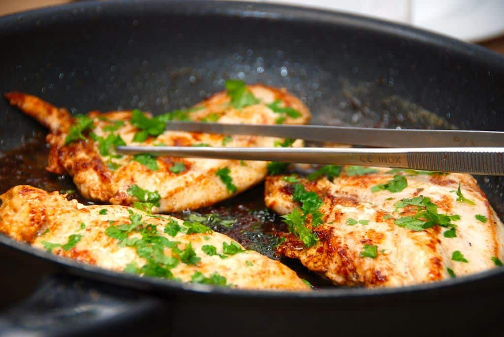 Pandestegt kyllingefilet, der anrettes med lidt frisk persille. Du laver det lækre kylling ved at slå kyllingebrysterne flade med en kagerulle, inden de steges møre i lidt smør på en meget varm pande. Foto: Guffeliguf.dk.