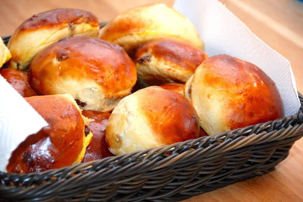 Skønne og lækre rosinboller, der bages med smør. Pensl med bollerne med sammenpisket æg, så de får en flot bageskorpe under turen i ovnen. Foto: Guffeliguf.dk.