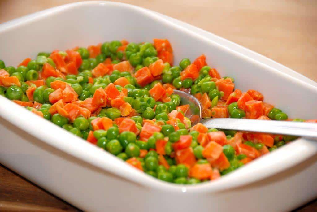 Flødestuvede ærter og gulerødder er nemt tilbehør til kødretter. Ærter og gulerødder svitses først, inden fløden tilsætter og cremer ind. Foto: Guffeliguf.dk.