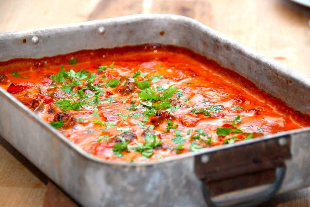 Koteletter i ovn laves i fad med løg, champignon og peberfrugter. Koteletterne ligger i en dejlig paprikaflødesovs. Foto: Madensverden.dk.