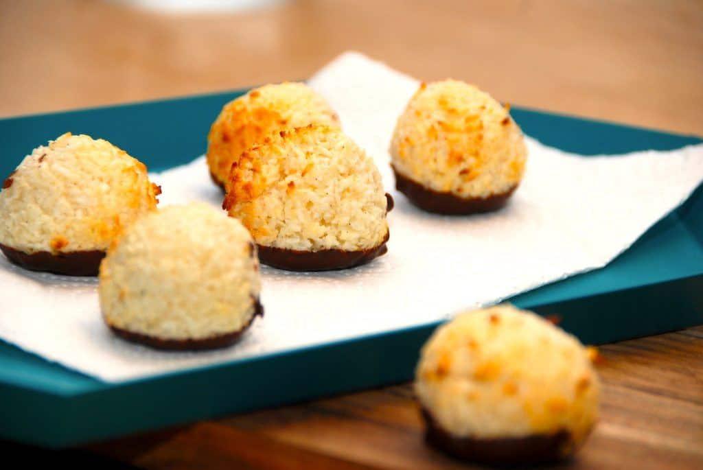 Saftige og lækre kokosmakroner, der også kaldes for kokostoppe. Kokosmakronerne dyppes i lidt chokolade, og så er de klar til spisning. Foto: Guffeliguf.dk.