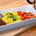 Perfekte scrambled eggs, eller røræg på dansk. Her anrettet til to personer med fire små tomater, fire brunchpølser, fire skiver bacon og rugbrød, Æggene drysses selvfølgelig med friskklippet purløg. Foto: Guffeliguf.dk.