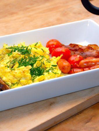 Perfekte scrambled eggs, eller røræg på dansk. Her anrettet til to personer med fire små tomater, fire brunchpølser, fire skiver bacon og rugbrød, Æggene drysses selvfølgelig med frisk purløg. Foto: Madensverden.dk.