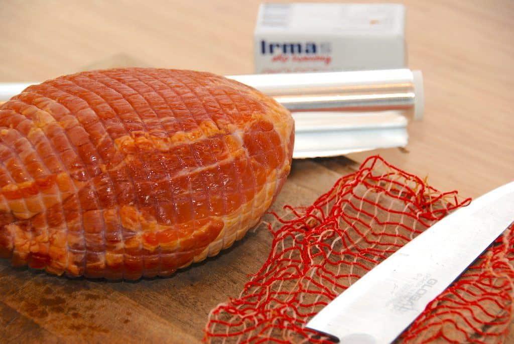 Det er godt at lave skinke i ovn, da det giver en saftig og mør skinke. Skinken pakkes ind i sølvpapir, der smøres med smør. Men husk at pille nettet af skinken først. Foto: Guffeliguf.dk.