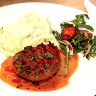 Sådan anretter du hakkebøffer i fad med peberflødesauce, som serveres med kartoffelmos og tomatsalat. Foto: Madensverden.dk.