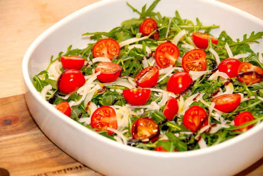 Farverig og indbydende ser den ud, og alligevel er det verdens nemmeste salat med rucola. Blandet med lidt små tomater, løg, balsamico og olivenolie. Den er klar på et par minutter. Foto: Guffeliguf.dk.